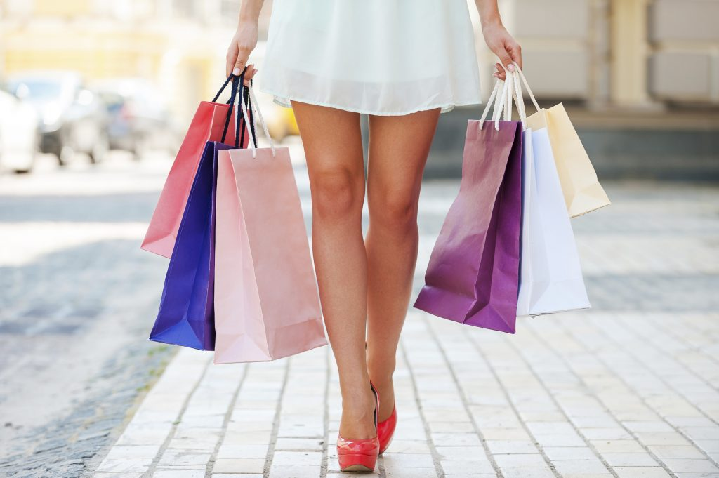 Close-up of young woman carrying shopping bags while walking along the street